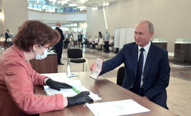Russian President Vladimir Putin shows his passport while taking part in a nationwide vote on amendments to the Russian Constitution during the main day of the vote at a polling station in Moscow, Russia, July 1. Photo by Alexei Druzhinin/EPA-EFE