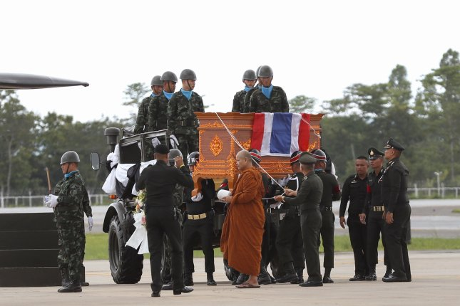 A Buddhist monk leads military honor guards carrying a flag-draped coffin with the body of former naval diver Saman Kunan, who died Friday trying to help rescue stranded boys in a Thai cave. Photo by Rungroj Yongrit/EPA-EFE