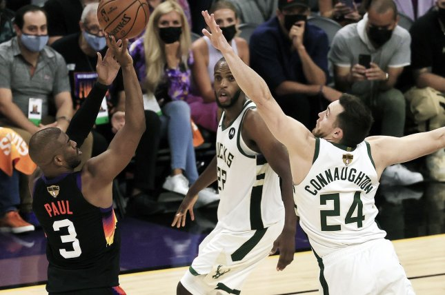 Phoenix Suns guard Chris Paul (L) shoots over Milwaukee Bucks defender Pat Connaughton (R) during the second half in Game 1 of the 2021 NBA Finals on Tuesday at Phoenix Suns Arena in Arizona. Photo by Tannen Maury/EPA-EFE