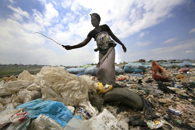 An Ivorian woman collects plastic bottles to sell for recycling from the general waste at the Akouedo recycling depot and landfill site in Abidjan, Ivory Coast, in 2018. There is expected to be more plastics than fish in the ocean by 2050. Photo by Legnan Koula/EPA-EFE