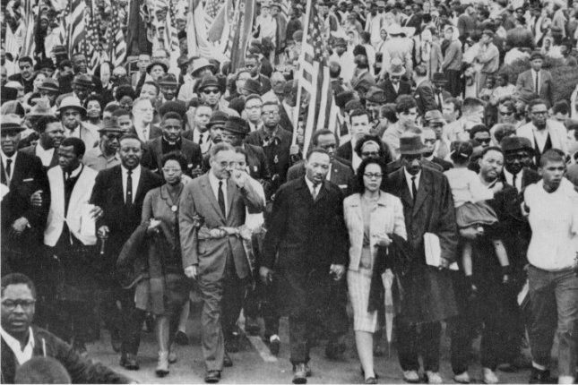 Dr. Martin Luther King leads an estimated 10,000 or more civil rights marchers out on last leg of their Selma-to-Montgomery march on March 25, 1965. UPI File Photo