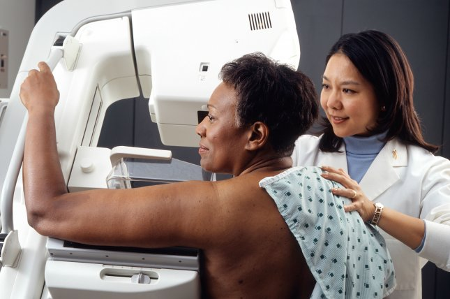 A technician positions a woman at an imaging machine to receive a mammogram. File Photo by Rhoda Baer/Wikimedia Commons