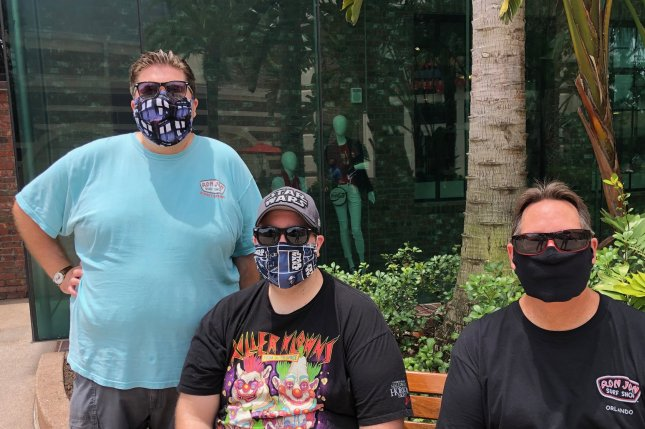 Cassidy, Bryan and Bill Corroa of Orlando visit Disney Springs on Friday. Face masks, signs and temperature checks are required.  Photo by Paul Brinkmann/UPI