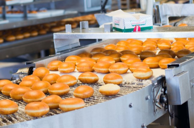 A man arrested after police mistook frosting from a Krispy Kreme doughnut, pictured coming off the baking line, for methamphetamine is suing the city and the maker of the drug test used to arrest him because he should not have spent 10 hours in jail for possession of donut glaze. Photo by Allen.G/Shutterstock.com
