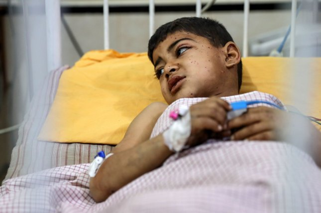 A 6-year-old boy lies in bed at a hospital in Douma, Syria, after he was injured by a cluster bomb. Doctors had no choice but to amputate both of the boy's legs. File Photo by Mohammed Badra/EPA-EFE