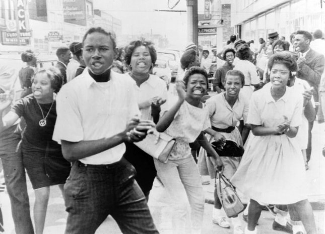 Protesters jeer at policeman standing with photographer in on May 7, 1963, as bands of demonstrators marched until police ordered fire trucks to the scene and hosed them down. On May 11, 1963, bombings in Birmingham, Ala., against non-violent Civil Rights campaigners triggers a crisis which leads to the involvement of federal troops. UPI File Photo