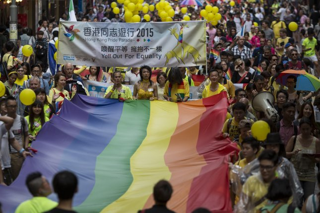 Participants carry a rainbow flag during the Hong Kong Pride Parade in Hong Kong, China, on November 7, 2015. On Wednesday, the high court ruled same-sex couples living in city have the same rights to spousal visas as married heterosexual couples. File Photo by Jerome Favre