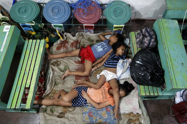 Filipino villagers rest inside a school in Naga city, Camarines Sur, Philippines, on Saturday, as Typhoon Goni prepares to make landfall in southern Luzon island. Photo by Francis R. Malasig/EPA-EFE