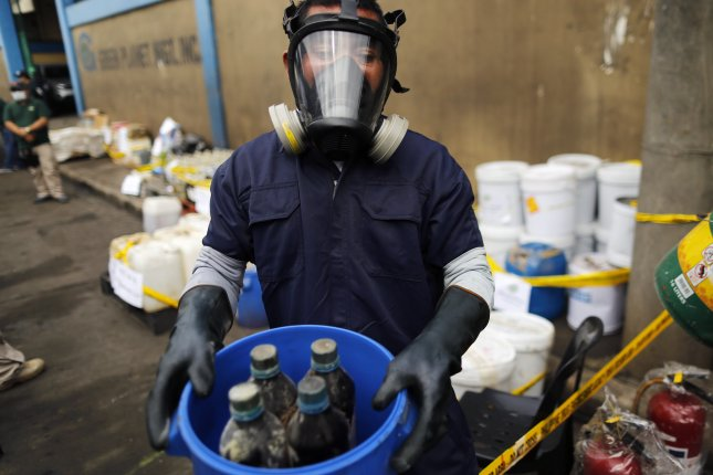 An operative of the Philippine Drug Enforcement Agency shows bottles of chemicals during a 2016 raid at a warehouse in Valenzuela City, north of Manila, Philippines. File Photo by Francis Malasig/EPA-EFE