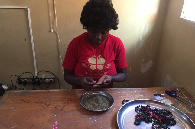 Makilene Velnis works at her desk to create beaded jewelry as part of the Papillon Enterprise's Apparent Project in Port-Au-Prince. Photo by Fariba Pajooh