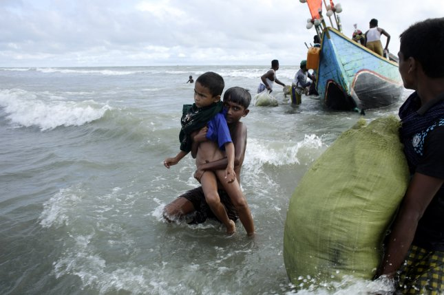 A Rohingya boy carries his brother toward shore of the Naf River as people arrive by boats in Teknaf, Bangladesh. File Photo by Abir Abdullah/EPA-EFE