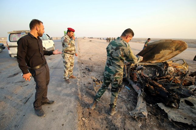 Iraqi police officers inspect the remains of a car used in a bomb attack in Nasiriyah, Iraq, on September 14 claimed by the Islamic State. The Justice Ministry said 38 Islamic State prisoners were executed in the city Thursday. Photo by Haider Al-Assadee/EPA