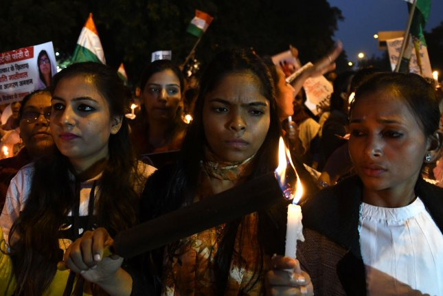 Indian women's rights activists reflect during a candlelight march to denounce violence against women, in New Delhi, India, Saturday. The protest comes a day after a young Indian woman died from her injuries after being set on fire while going to trial against her alleged rapist. Photo via EPA-EFE