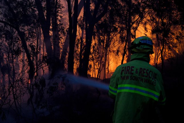 Fire and Rescue NSW firefighters conduct property protection as a brushfire burns close to homes on Railway Parade in Woodford, New South Wales, Australia, on November 8. Photo by Dan Himbrechts/EPA-EFE