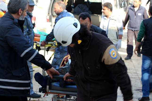 Rescue workers with the volunteer White Helmets group aid victims of a car bomb attack in Idlib, Syria, in  2017. File Photo by EPA-EFE