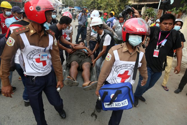 An injured man is carried on a stretcher by medical staff after police fired at demonstrators in Mandalay Saturday during a protest against the military coup. Photo by Zaw Hein/EPA-EFE