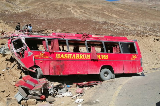 People stand beside the wreckage of a passenger bus at the scene of its accident in the semiautonomous Gilgit-Baltistan region of Pakistan on Sunday. Photo by Meraj Alam/EPA-EFE