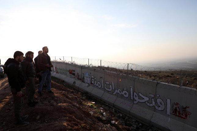 A group of Syrian civilians look over the border wall and into Turkey from Idlib province, Syria, on February 2. More than a half-million Idlib residents have attempted to flee fighting over the last several weeks. Photo by Yahya Nemah/EPA-EFE