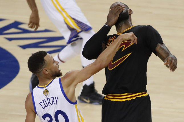 b058ceeb3d14 Golden State Warriors guard Stephen Curry (L) hits Cleveland Cavaliers  forward LeBron James (R) while taking a shot in the first half of Game 2 of  the NBA ...