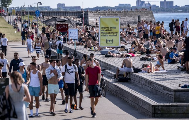 People stroll, sunbathe and swim at a bathing jetty in Malmo, Sweden, in June. The country attempted to achieve COVID-19 herd immunity by skipping lockdowns and other measures most countries around the world are using to limit spread of the disease. Photo by EPA-EFE/Johan Nilsson/TT