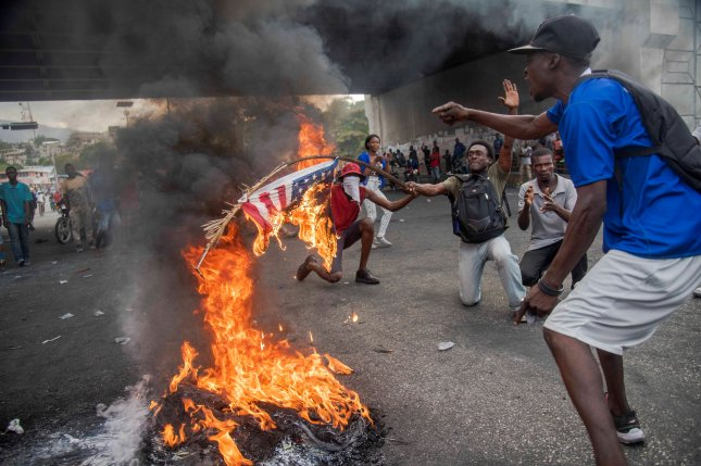 Protesters participate in an anti-government rally in Port-au-Prince, Haiti, including burning an American flag. During a week of protests, demonstrators have called for the resignation of President Jovenel Moise. Photo by Jean Marc Herve/EPA