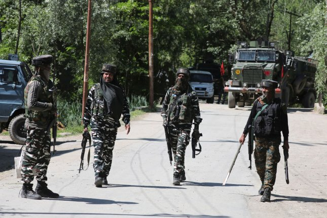Indian paramilitary soldiers walk near site where a gunfight took place in the village of Beighpora in south Kashmir's Pulwama district on Wednesday. Photo by Farooq Khan/EPA-EFE
