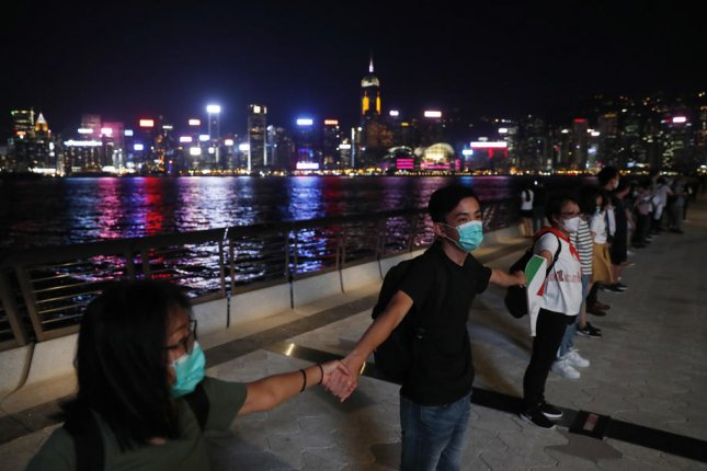Protesters hold hands in Hong Kong Friday for a protest inspired by a similar staging 30 years ago. Photo by Roman Pilpey/EPA-EFE