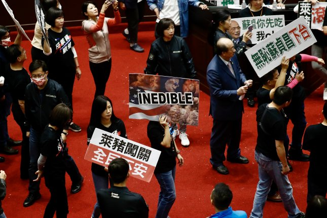Lawmakers from Taiwan's Kuomintang (KMT) party hold placards during a protest inside the parliament in Taipei, Taiwan on Friday. Tension escalated as opposition lawmakers protested against the current pork importation from the United States and asked for Premier Su Tseng-chang to step down. Photo by Ritchie B. Tongo/EPA-EFE
