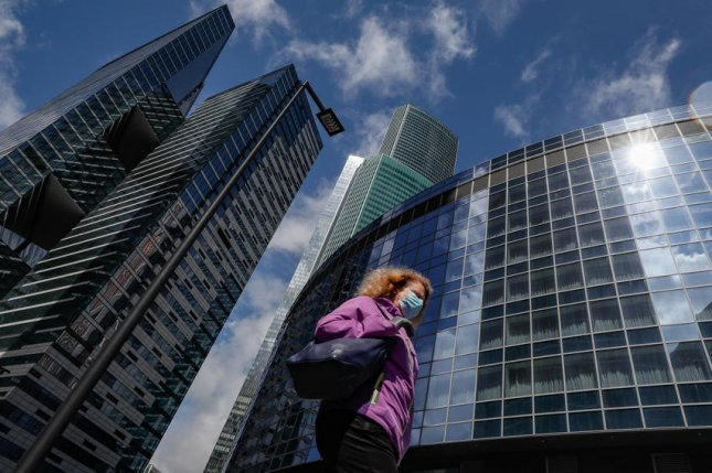 A masked woman passes an office tower in Moscow, Russia, on May 2. The IMF warned earlier this summer that global growth could contract by nearly 5% and imperil significant progress made since the 1990s. File Photo by Yuri Kochetkov/EPA-EFE