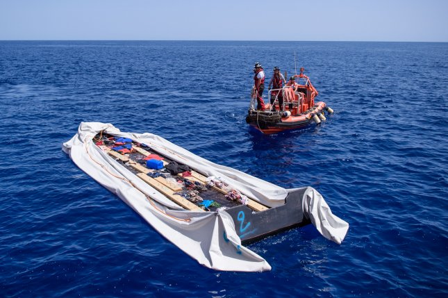 Members of a humanitarian organization observe an empty rubber boat used by migrants to cross the Mediterranean Sea. A similar vessel capsized this week off the coast of Libya, killing an estimated 100 migrants. File Photo by Christophe Petit Tesson/EPA-EFE