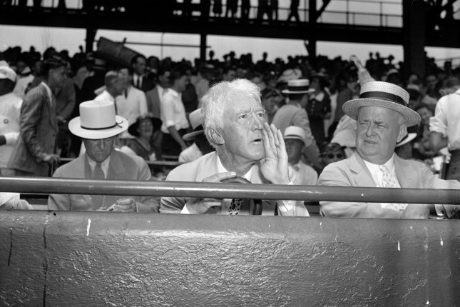 Judge Kenesaw Mountain Landis, commissioner of baseball, assumes his characteristic pose for the cameramen as he takes in the 1937 All-Star game in Washington, D.C., on July 7, 1937. On January 12, 1921, Landis was elected the first commissioner of Major League Baseball. File Photo by Library of Congress/UPI