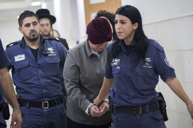 Malka Leifer (2-R) is seen handcuffed while being brought to Jerusalem District court on February 14, 2018. The court ruled Tuesday she is mentally fit for extradition to Australia to face 74 counts of child sexual abuse. File photo by EPA-EFE