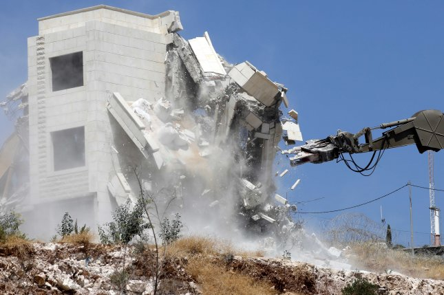 An Israeli army excavator machine demolishes a building Monday in the Palestinian village of Sur Baher, in East Jerusalem. Photo by Al Haslamoun/EPA-EFE