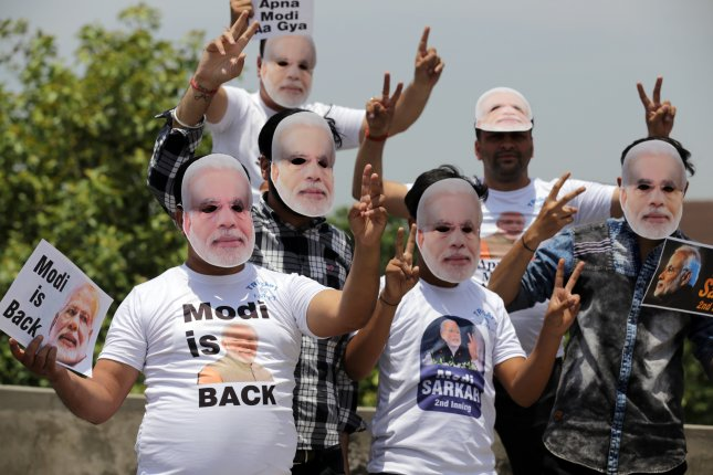 Bharatiya Janata Party (BJP) supporters wearing masks depicting Indian Prime Minister Narendra Modi celebrate the BJP's predicted win in parliamentary elections in Amritsar, India. Photo by Raminder Pal Singh/EPA-EFE