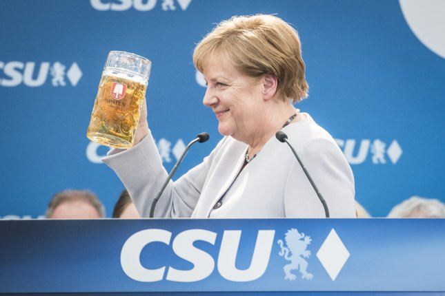 German Chancellor Angela Merkel toasts with a beer during an election campaign event Sunday of the German Christian Social Union party in Munich, Germany. Photo by Christian Bruna/EPA