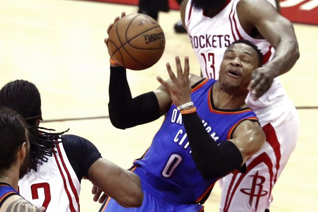Oklahoma City Thunder guard Russell Westbrook (C) is fouled by Houston Rockets guard James Harden (R) while going to the basket in the first half of Game 2 of the NBA Western Conference playoffs on April 19 at the Toyota Center in Houston, Texas. Photo by Larry W. Smith/EPA