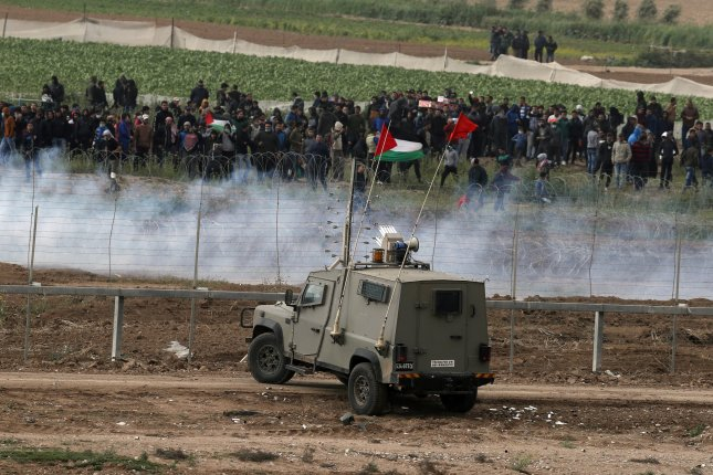 Palestinian protesters from Gaza strip and Israeli soldiers clash Saturday at the security fence next to Nahal Oz, facing the Gaza neighborhood of Shjaaia. Photo by Atef Safadi/EPA
