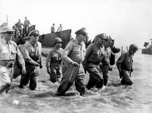General Douglas MacArthur and staff, accompanied by Philippine president Sergio Osmena (right), land at Palo Beach, Leyte, on Oct. 21, 1944. Less than four months later, Americna forces, led by MacArthur, would enter the Philippine capital of Manila, liberating it from the Japanese. File Photo by US Army/UPI