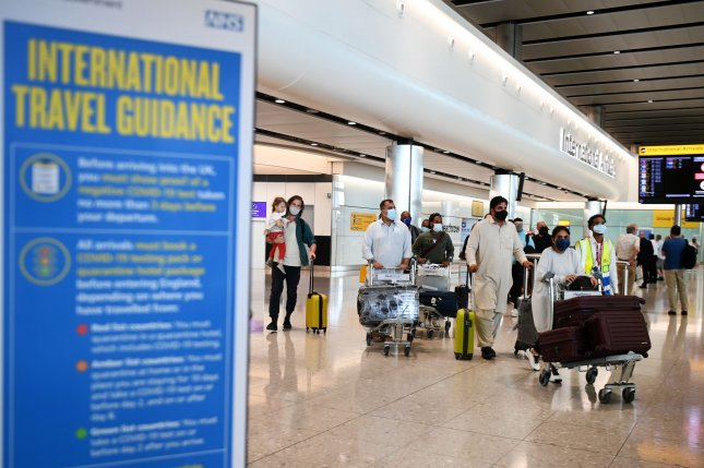 Travelers arrive at the Heathrow airport in London on June 8 greeted by a sign for travel guidance. Heathrow will start accepting U.S. travelers who have been vaccinated by the end of the month. File Photo by Andy Rain/EPA-EFE