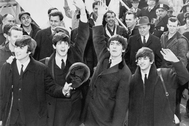 The Beatles wave to the thousands of screaming teenagers after their arrival at Kennedy Airport in New York City on February 7, 1964. On January 30, 1969, the Beatles staged an impromptu concert on the roof of Apple Records in London in the last public appearance by the band. File Photo by UPI