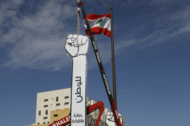 Workers install two fists as symbol of the October revolution in front of the Al-Amin Mosque in downtown Beirut, Lebanon, on October 22. File Photo by Nabil Mounzer/EPA-EFE