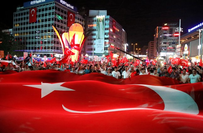 People hold a large Turkish flag during a march to mark the first anniversary of a coup attempt in 2016. The Turkish government fired 18,000 state employees Sunday, citing alleged terrorist ties in relation to the failed coup. Photo by STR/EPA