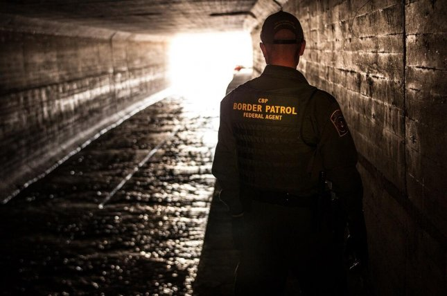 Border Patrol agent inspects a water drainage tunnel from Nogales, Ariz., into Mexico in an undated photo. Customs and Border Protection said Thursday and arrests and detentions in June increased from May, but down from the same time last year. Photo by John Denmark/U.S. Customs and Border Protection-UPI