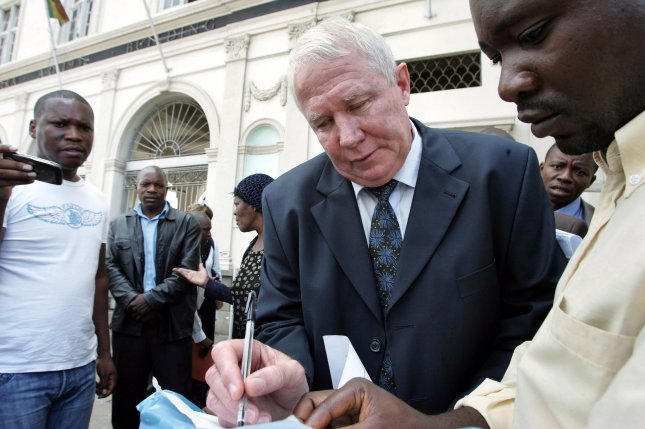Zimbabwe's Movement for Democratic Change Roy Bennett signs a summons issued to him outside the high court in 2010. The Zimbabwe opposition figure died Wednesday in a New Mexico helicopter crash. File Photo by Aaron Ufumeli/EPA