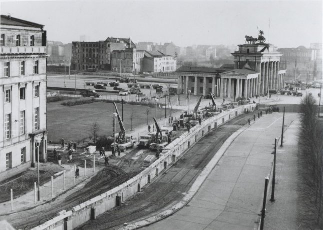Under the watchful eye of the Communist police, East German workers near the Bradenburg Gate reinforce the wall dividing the city in October 1961. Since erecting the wall on August 13, 1961, to stop the flow of East Germans into West Berlin, the East German Communists have added bunkers, spotlights and firing and observation posts. Photo by IPS/U.S. Archives/UPI