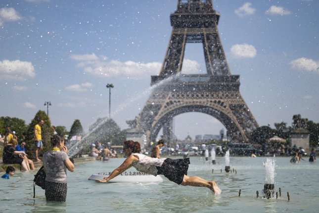 People cool down in the fountains of Trocadero, across from the Eiffel Tower, during a heatwave in Paris June 25, 2019. A United Nations weather organization said temperatures could rise faster than expected over the next five years. Photo by Ian Langsdon/EPA-EFE