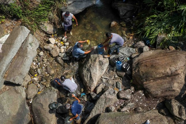 People collect water at the El Avila National Park in Caracas, Venezuela, on Monday. Maduro said the electricity rationing should also help water scarcity as the country's water pumps have failed during blackouts. Photo by Miguel Gutiérrez/EPA-EFE