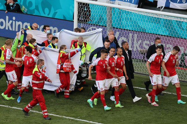Teammates shielded Christian Eriksen of Denmark as he received medical attention for cardiac arrest during a UEFA Euro 2020 match against Finland on Saturday in Copenhagen, Denmark. Photo by Wolfgang Rattay/EPA-EFE