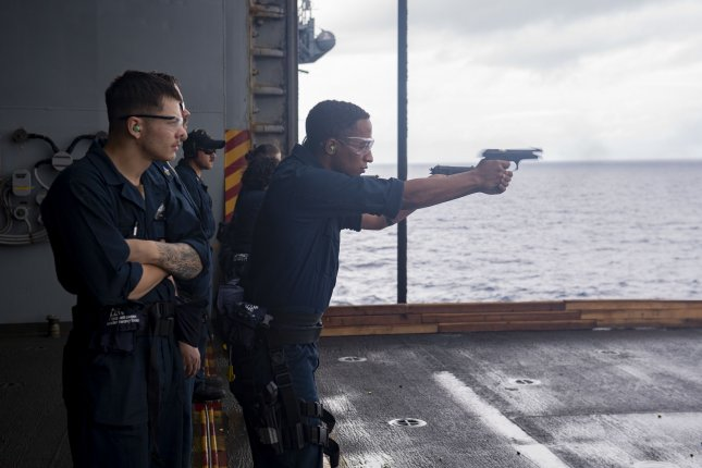 Bismarck Sea Sailors assigned to the forward-deployed amphibious assault ship USS America conduct a small arms gun shoot on the ship's starboard aircraft elevator. Photo by Jomark A. Almazan/U.S. Navy