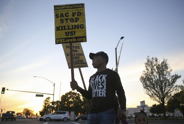 People attend a rally and vigil on March 31 for Stephon Clark, who was fatally shot last month by police in Sacramento, California. On Tuesday, state lawmakers proposed a bill to redefine the standard for when police may use deadly force. Photo by Elijah Nouvelage/ EPA-EFE